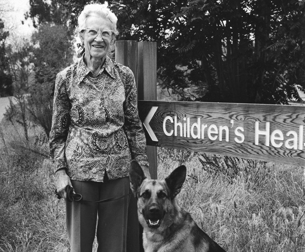 Woman with dog by sign outdoors